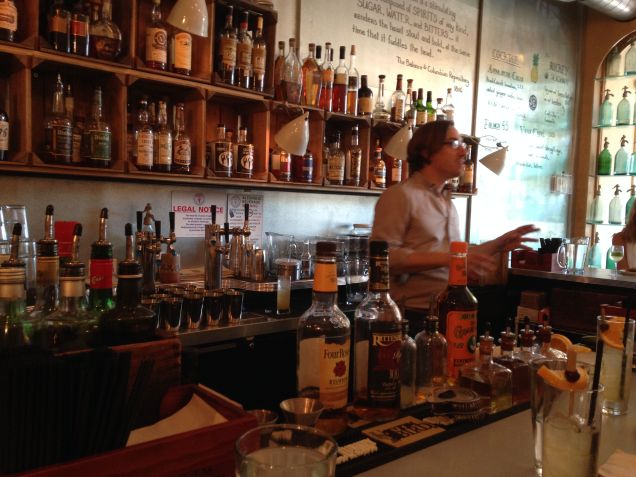 Derek Brown behind the bar, well stocked with Southern bourbons and whiskeys.